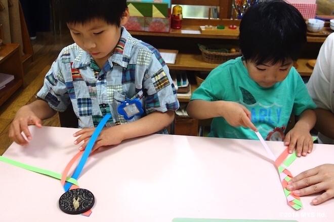 紙で三つ編みを練習する子