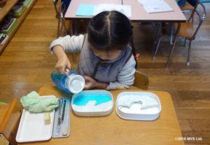 紙粘土で作った対照地形に色水を流し込む子