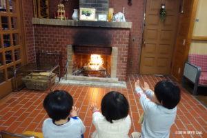玄関の暖炉で暖まる子たち
