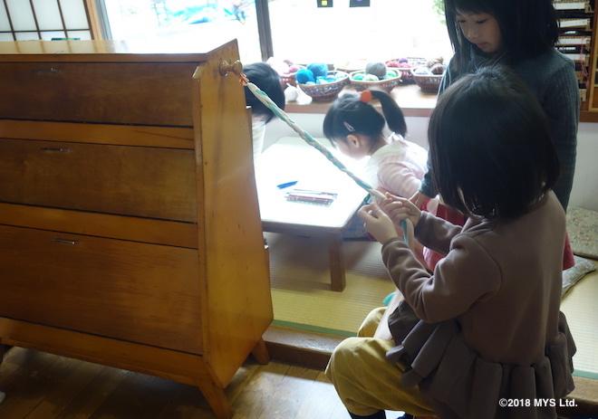 布で三つ編みを練習する子