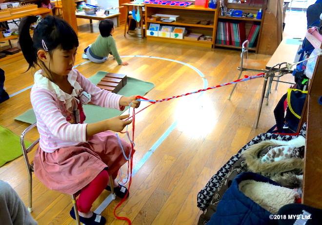 毛糸の束で三つ編みの練習をする子