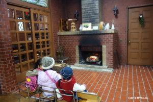 暖炉で暖まる子たち