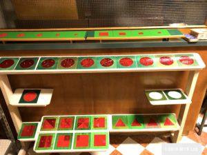 メタルインセット / 幾何図形をくり抜いた緑の正方形の枠に赤い幾何図形ががはめ込まれた、鉄製の教材