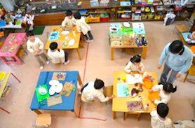 ピンク、青などの机の周りでお仕事をする子どもたち。恵泉幼稚園の教室の様子。