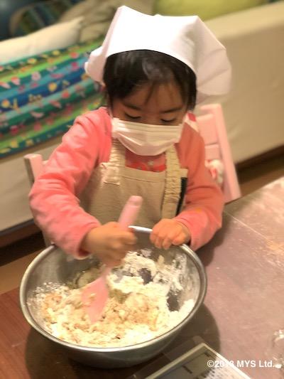子供がゴムベラでボールの中のパンの材料を混ぜているところ