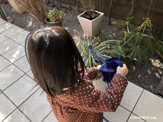 外の植木に水やりをする子供