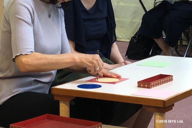 丸いメタルインセットの枠を使って、鉛筆で丸を描く女性