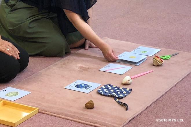 コマの前にクルミのイラストと文字が書かれたカードを置こうとする女性