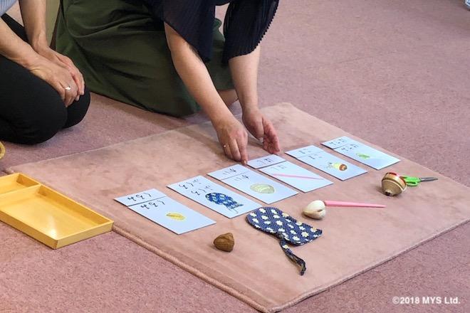 ハサミ、コマ、箸、貝、袋、クルミの実物の前にそれぞれのイラストと文字が書かれたカード