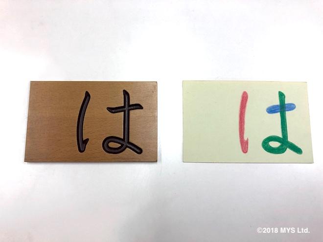 ひらがなが彫られたカードと、ひらがなの書き順が色分けされたカード