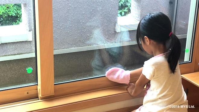 窓拭きで枠に垂れた水をミトンで拭く子供