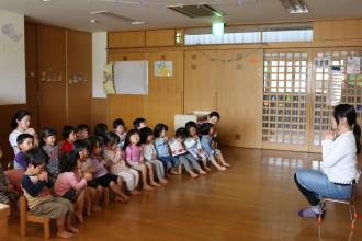 先生と向かい合ってお祈りする子供たち