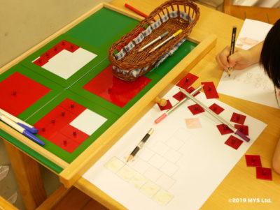 Taipei Utopia Montessori Elementary School で分数の教具を使って絵を描く生徒