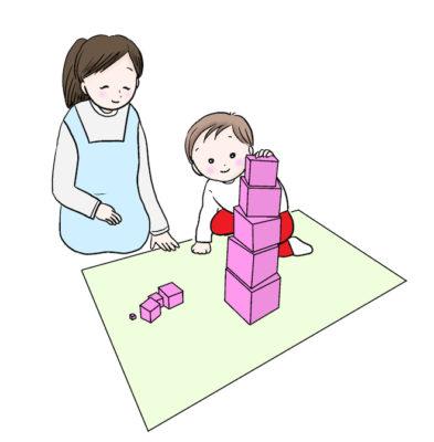モンテッソーリ教具ピンクタワーで遊ぶ子供とそれを見守る保育士