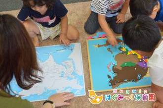 モンテッソーリ教育のアジアの地図パネルの活動をする子供