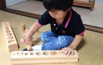 モンテッソーリ教育のはめ込み円柱をする子ども