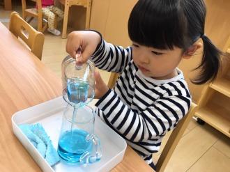 市川なないろ保育園で色水を注ぐ子ども