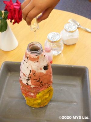 モンテッソーリ教育の地理学で噴火を学ぶため容器に洗剤を入れる様子